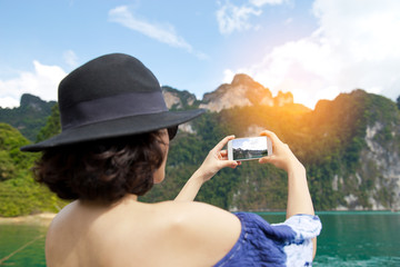 Selective focus on phone. Back view of woman  Wearing stylish blue dress and stylish hat.   taking pictures of in Khao Sok lake or sea.