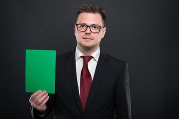 Portrait of business man holding green cardboard.