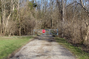 The closed metal gate to the gravel road in the woods.