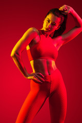 A strong athletic, woman dancer, posing on red background wearing in the sportswear, fitness and sport motivation with copy space.