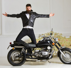 Superiority concept. Hipster biker brutal in leather jacket on motorcycle enjoying richness. Man, bearded biker in leather jacket near motor bike in luxury living room interior background.
