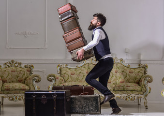 Macho elegant accidentally stumbled, dropping pile of vintage suitcases. Butler and service concept. Man with beard and mustache wearing classic suit delivers luggage, luxury white interior background