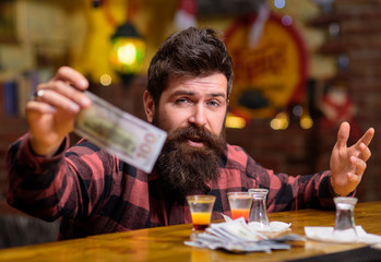 Hipster holds money, cash to buy more alcohol.