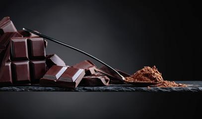 Broken chocolate pieces and cocoa powder on black background.