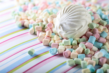 Close up of various marshmallows on a striped background.