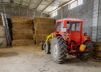 tractor in a shed with haystacks