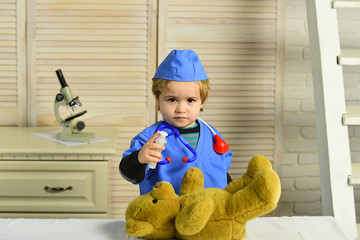 Kid in doctor coat makes injection to teddy bear.
