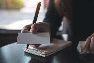 Businesswoman giving and showing an empty business card while writing down on a notebook