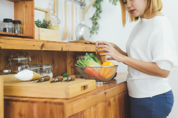Asian woman making healthy food standing happy smiling in kitchen preparing salad. Beautiful cheerful Asian young woman at home. Healthy food dieting and healthy lifestyle cooking at home Concept.