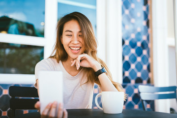 Attractive beautiful happy young Asian woman taking a selfie using a smart phone at cafe. Young Asian girl at restaurant taking self portrait.