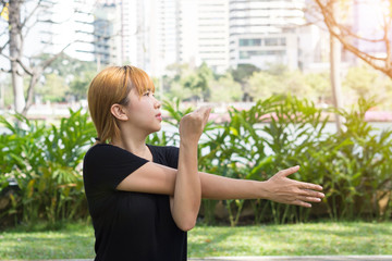 Young asian woman warm up her body by stretching her arms to be ready for exercising and do yoga in the park surrounded by nature and warm light afternoon sky. Outdoor workout exercise concept.