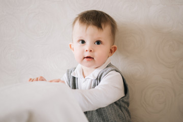 Happy cute boy in a gentleman's suit stands near the support on a light background, trying to get up, learning to walk.
