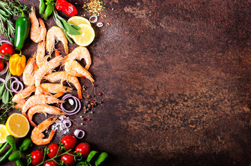 Fresh fish, shrimps with herbs, spices and vegetables on dark vintage background. Healthy food, diet or cooking concept.