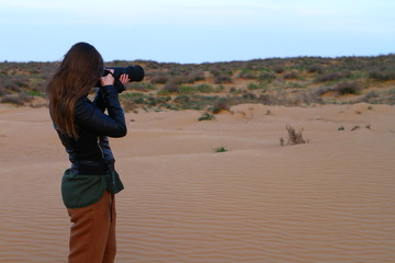 Photographer girl is taking shots on the desert sand on sunset in summertime