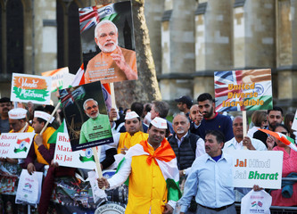 Demonstrator holds a placards and pictures of India's Prime Minister Narendra Modi in Parliament Square, London