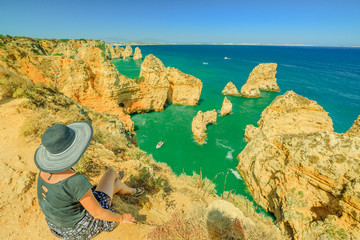 Summer holidays in Algarve, Portugal. Lifestyle tourist with hat sitting on promontory of Ponta da Piedade and overlooks the coast of Lagos with iconic cliffs and limestone. Turquoise sea, sunny day.