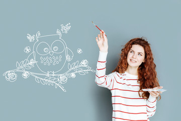 Lovely detail. Beautiful talented creative designer smiling and carefully holding a brush while painting a cute little owl