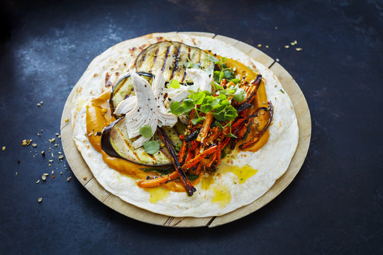 Pulled Chicken Wrap, carrot, grilled aubergine, curry hummus and herbs on chopping board