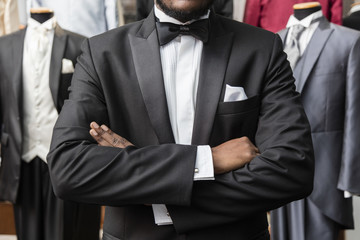 Black man dressed with a tuxedo, crossing arms