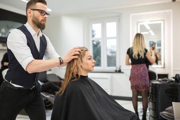 Hairdresser applying conditioner on customer hair