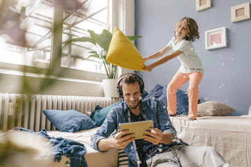 Father and son having pillow fight at home