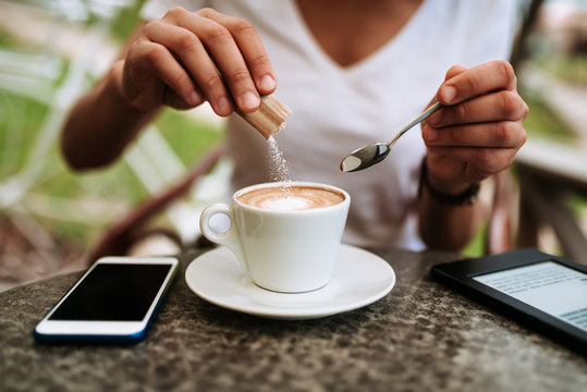 Young woman adding white sugar to the coffee.