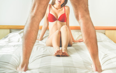 Young woman looking man standing up on the bed - Sexual relationship, cheating, female underwear and male power concept - Handsome couple ready to having sex