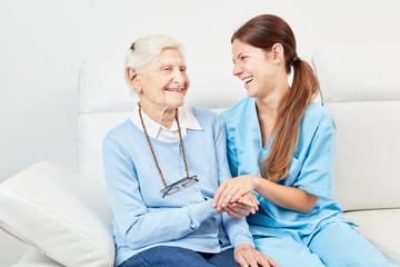 Glückliche Seniorin und Frau vom Pflegedienst