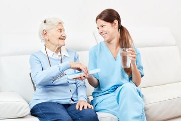 Seniorin erhält ein Medikament von Pflegedienst