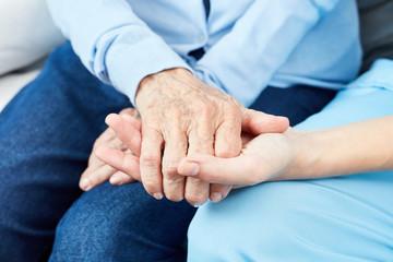 Altenpfleger hält tröstend Hand einer alten Frau