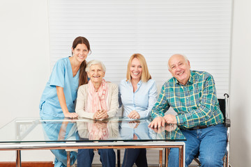 Pflegekraft und glückliche Familie im Seniorenheim