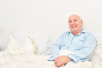 Lächelnder Senior als bettlägeriger Patient