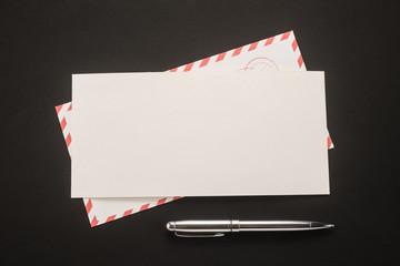 Envelope and pen on black background