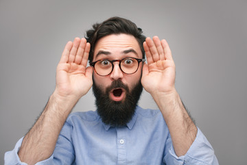 Amazed bearded man with hands up