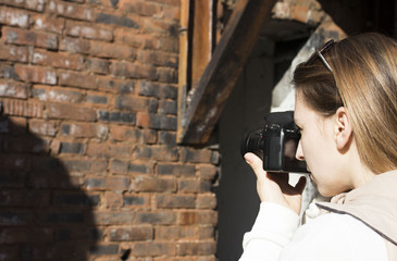 girl taking pictures with a camera abandoned, destroyed building