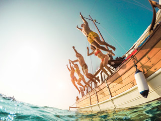 Group of happy friends diving from sailing boat into the sea - Young people jumping inside ocean in summer vacation - Travel and fun concept - Fisheye lens distortion