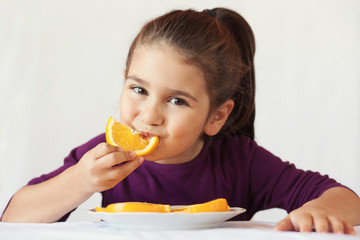 little cute child girl dressed in a purple blouse holding an orange and eating off a piece of orange