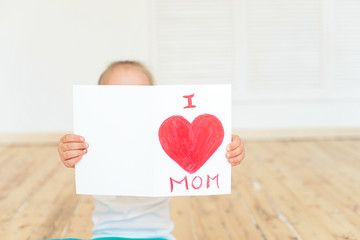 Little girl paints greeting card for Mom on Mother's Day with the inscription I love you mom . Indoors. Mother's Day concept.