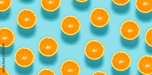 Wall mural Fresh orange halves on a blue background