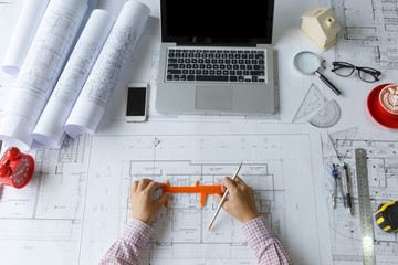 Top view, Architect hands working on blueprint plans. Architectural project, blueprints, ruler, dividers, laptop, tablet, smartphone and engineering tools.