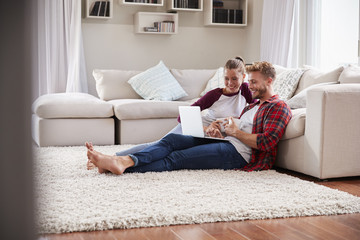 Young white couple sitting on the floor at home using laptop