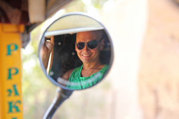 Reflection in a circular mirror. The male face is reflected in the mirror of the tuk tuk. A tourist man in sunglasses is reflected in a round mirror and smiles. Vijayanagar, karnataka, unesco