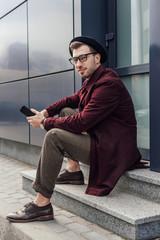 handsome trendy man using smartphone on street