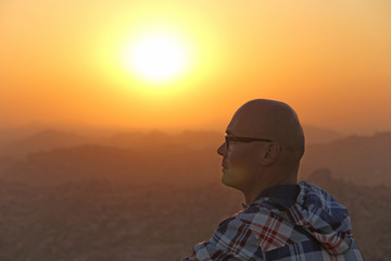 A handsome bald man in glasses sits on a sunset or dawn background in Hampi, India. Beautiful sunset or sunrise. Vijayanagar, karnataka, unesco