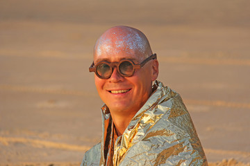 A bald and handsome man freak smiles in a golden cape or clothes and round glasses. An unusual male designer. A man is a freak at a festival or a freak parade. India, Goa