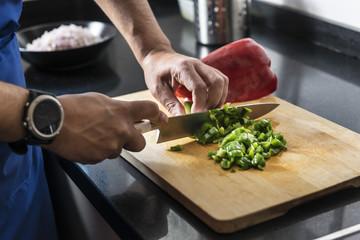 chef chopping green pepper on a cutting board