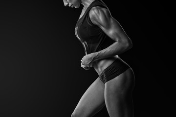 Confident athletic woman bodybuilder with sixpack abs posing Young fitness woman in sports clothing bra short standing with hands overhead Black and white close-up shot.