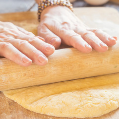 Woman kneading a dough whith rolling pin