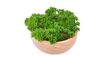 parsley in a wooden bowl isolated on white background