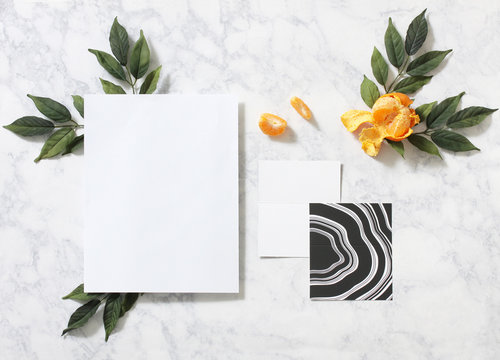 Decorative leaves with blank paper and orange fruit